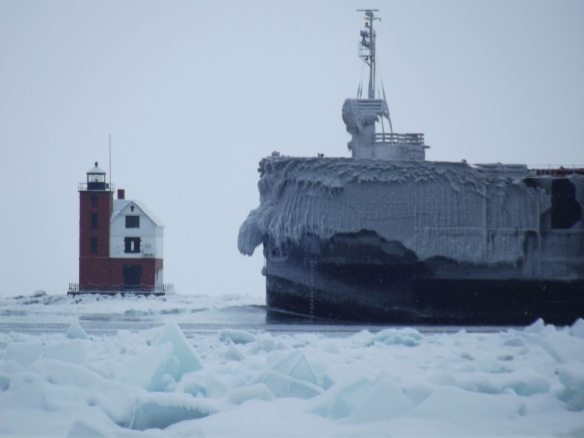 If this photo doesn't make you grab your winter coat, snowboots, muffler, and gloves, nothing will!  The icy freighter, American Century, makes what may be one of its last passes of the winter by the Round Island Lighthouse. (Photo: Greg Main)