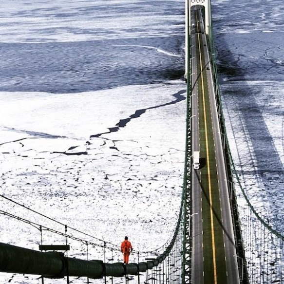 Ok - this scares the stew out of me!  A shot from one of the Mackinac Bridge towers (by the Michigan Department of Transportation) of the icy Straits of Mackinac AND one very brave soul walking down the suspension