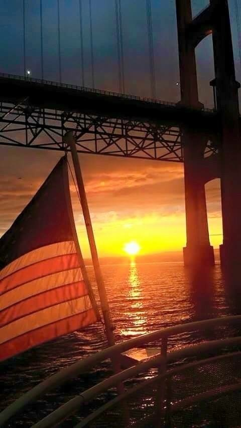 The 4th on Mackinac! A flag on a ferry's stern waves proudly as they pass under the Mackinac Bridge.