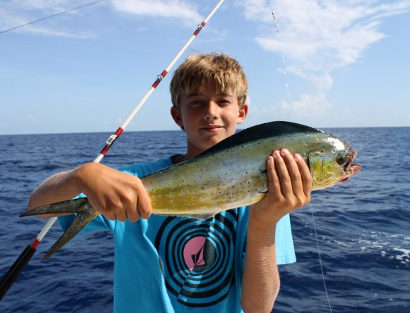 """We hooked and lost several fish before getting this small dolphin aboard (this is the dolphin you eat, not the """"Flipper"""" dolphin.  In seafood restaurants you would order it as Mahi-Mahi. This one went back into the ocean to grow some more."""