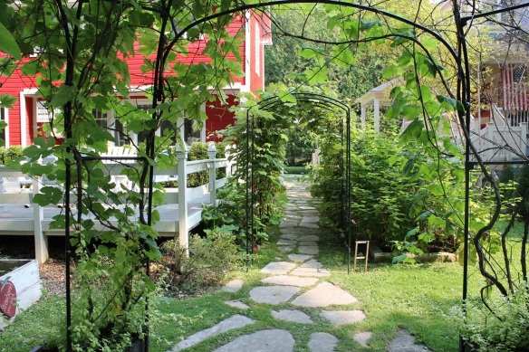 The entire back and side yard is a whimsical delight, filled with arches entwined with greenery . . .