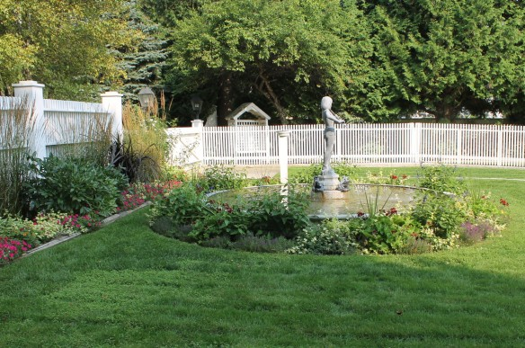 A beautiful fountain is a focal point in this back yard.